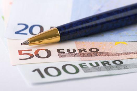 Euro banknotes and pen