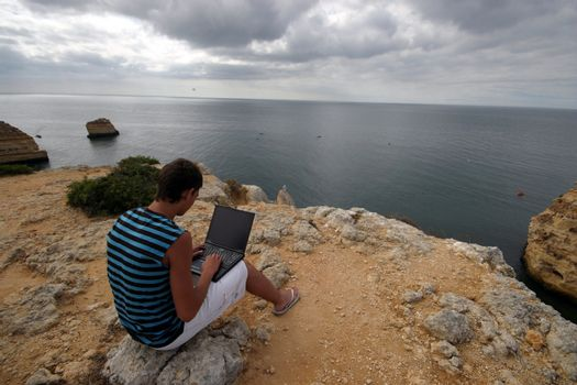 man working with laptop on the coast