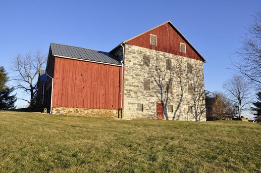 old stone and red wood barn in the country