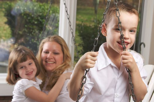 Young Boy Smiles for The Camera as His Mom and Sister Look On