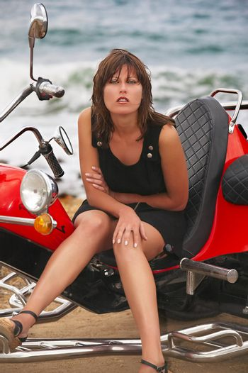 Young beautiful woman sits on trike