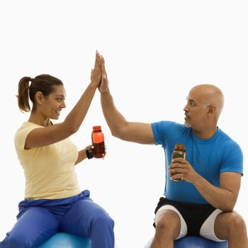 Mid adult multiethnic man and woman sitting on blue exercise balls giving each other the high five.