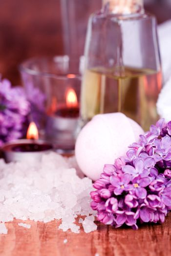 bath and spa items (salt, oil, lilac, candle) on wooden background