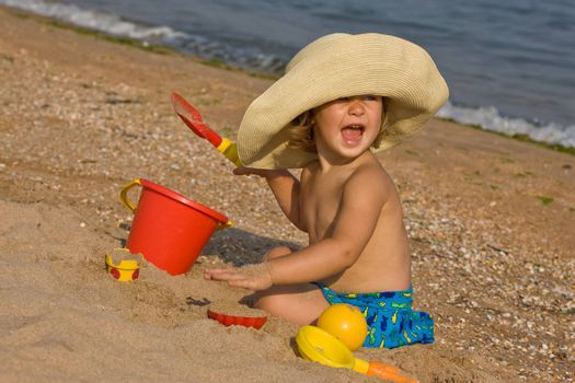 little girl in the bonnet plaing with sand
