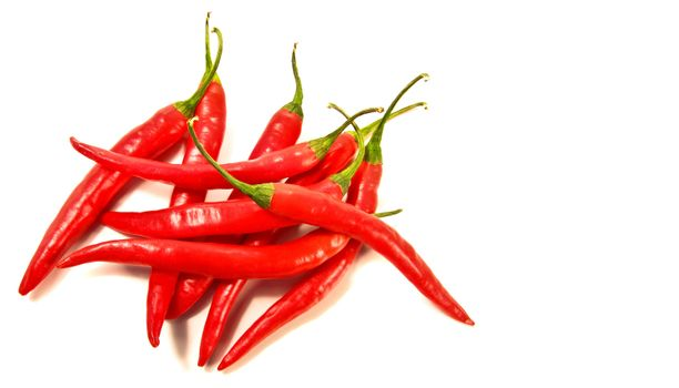 Red peppers laying against a white