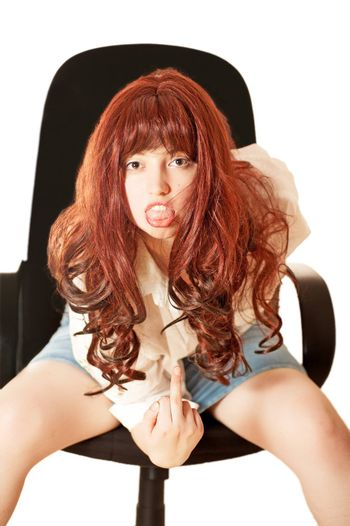 Young woman in armchair shows middle finger and tongue