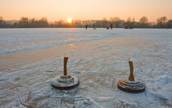 two curling stones on a frozen lake at sunset