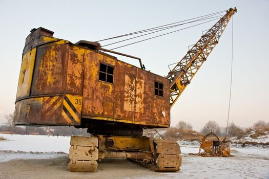 rusty old yellow excavator on a winter day