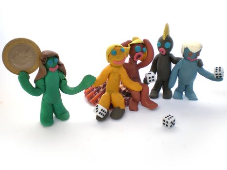 plasticine people figures playing with dice on white background
