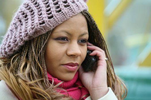 pretty african girl in lilac beret is talking on mobile telephone