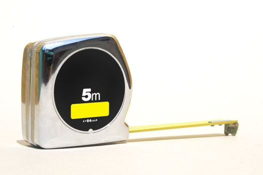 Silver retractable tape ruler against white background