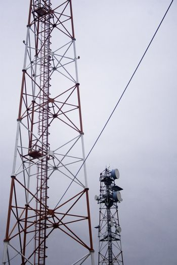 Two modern communication towers on overcast day