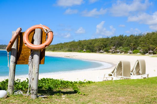 Safe swimming in paradise. Orange life buoys and white sand tropical beach.