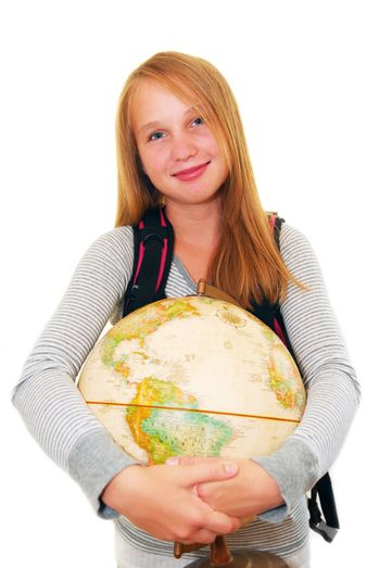 Young smiling school girl with a backback and a globe isolated on white background