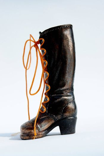 bronze boot on white background with orange lace