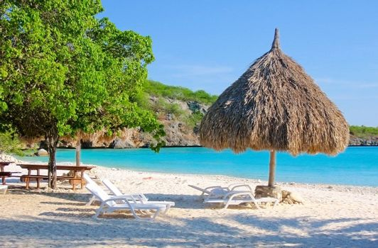 tropical beach with chairs and natural made parasol of palm leaves