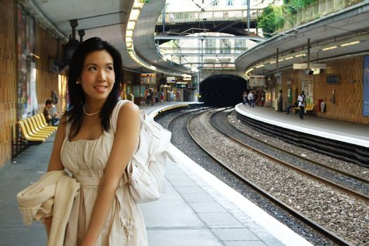 A woman waits for the train on the platform, perpective of the tracks on the right.