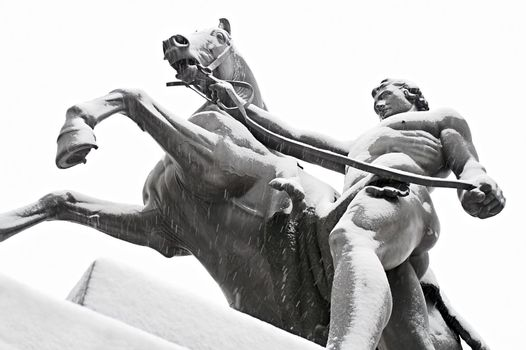 "One of the famous ""Taming of Horses"" public ensemble by Klodt at Anichkov Bridge in St. Petersburg. Russia, while snowing."