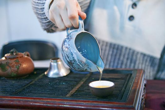 Man pouring green tea to traditional japanese cups