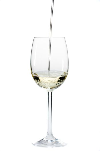 pouring white wine in a glass over a white background