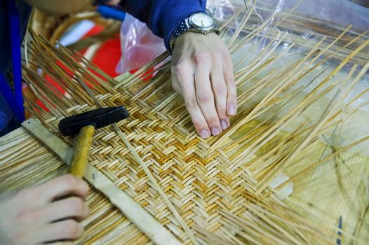 Boy doing traditional crafting work of basketry