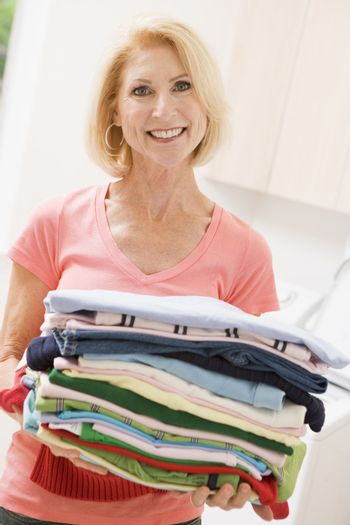Woman Carrying Folded Up Laundry