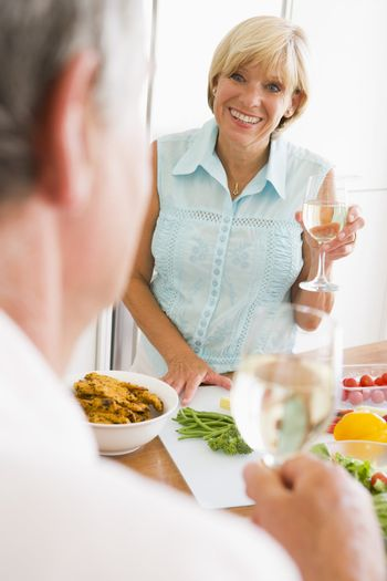Woman Talking To Husband As She Prepares A meal,mealtime