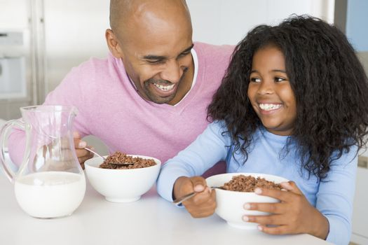 Father Sitting With Daughter As She They Eat Breakfast