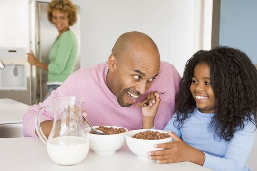 Father Sitting With Daughter As She They Eat Breakfast With Her