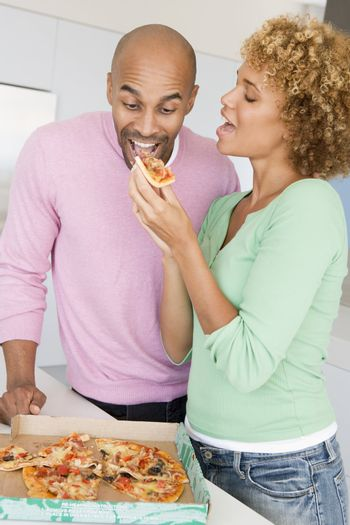Husband And Wife Eating Pizza