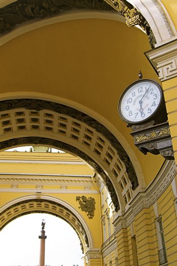 Old-style Public Clocks under the General Army Staff Building Arch in Saint Petersburg, Russia. The inscription on the clock-face: State Chamber for Measuring and Weighing (upper, 19th century designation, now out of use) and Exact Time (bottom).