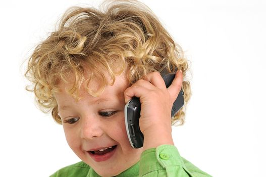 blond curly haired boy talking on mobile phone happy and smiling