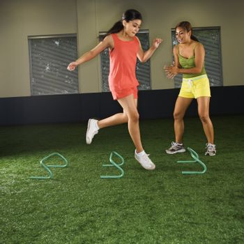 Girl jumping step hurdles in indoor gym while woman coach watches.