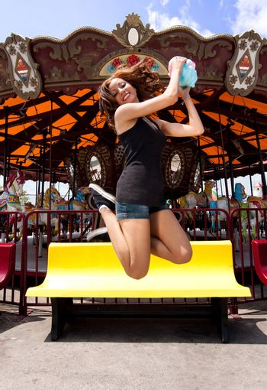 Fun girl jumping at Carousel