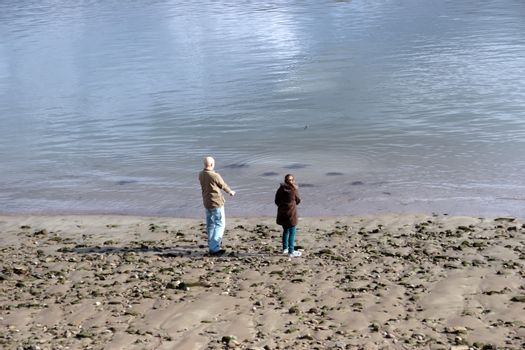 father and daughter skimming stones on the seashore