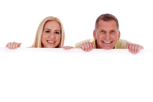Man and woman holding empty white board and smiling at camera