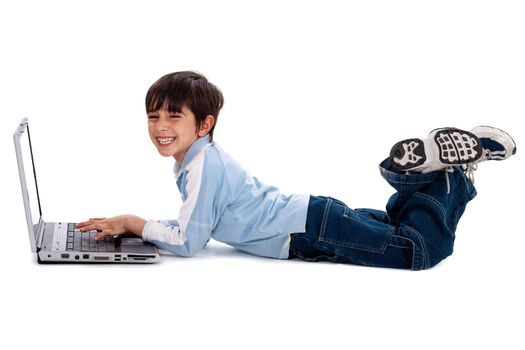 Young boy lying on floor and surfing on his laptop