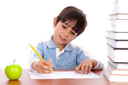 Cute young boy busy in drawing with pile of books beside him