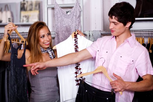 Happy young girl expecting her boy friends choice in fashion cloth retail store