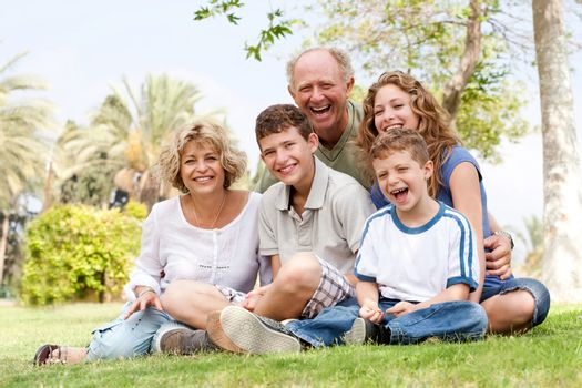 Happy family having fun in the park, smiling and enjoying sunny day