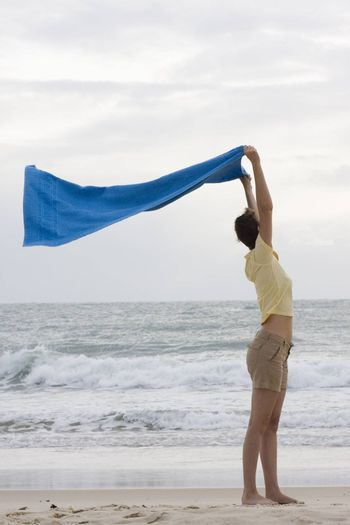 Woman holding a towel in the wind on a beach