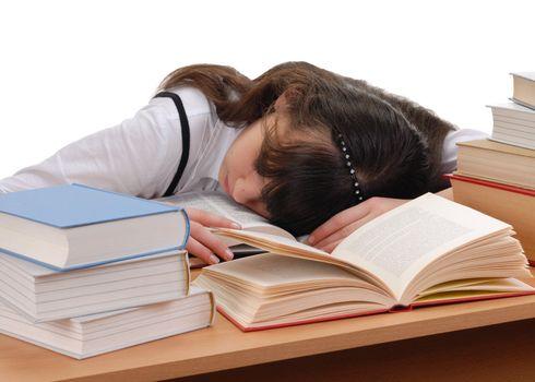 Tired schoolgirl sleeping on books