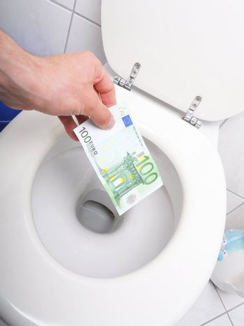 money and toilet showing financial crisis concept