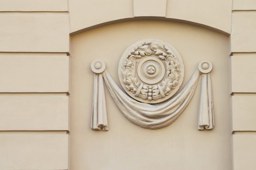 A close-up detail of a building facade decor. A moulded plastic panel. Early soviet-epoch style.