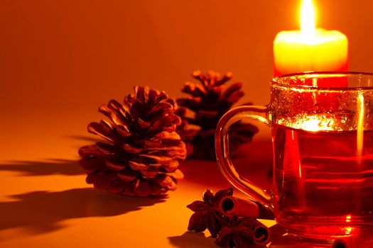 red tea cinnamon sticks star anise conifer cone at candle light