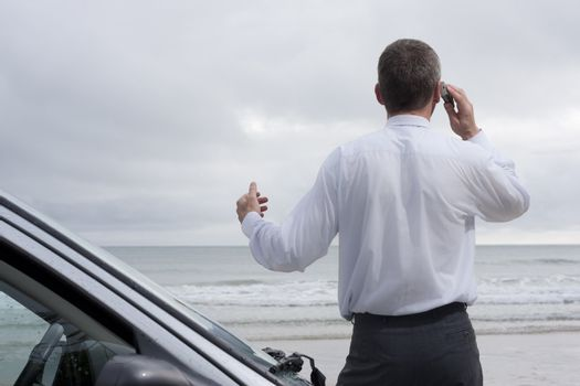 Businessman talking on mobile phone beside his car on a beach