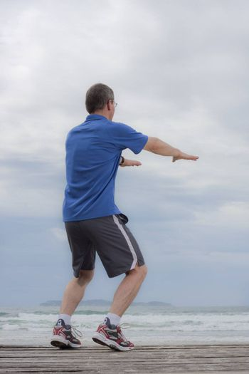 Runner doing gymnastics exercise on a beach