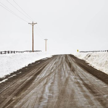 Muddy dirt road in rural, snow covered landscape with power lines.
