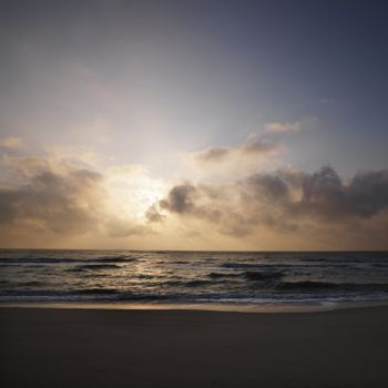 Beach with sun setting in clouds over ocean at Bald Head Island, North Carolina