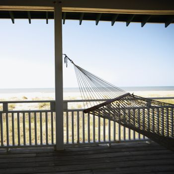 View of beach from porch with railing and hammock at Bald Head Island, North Carolina